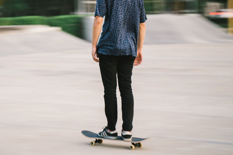 Low section of man standing on skateboard in city
