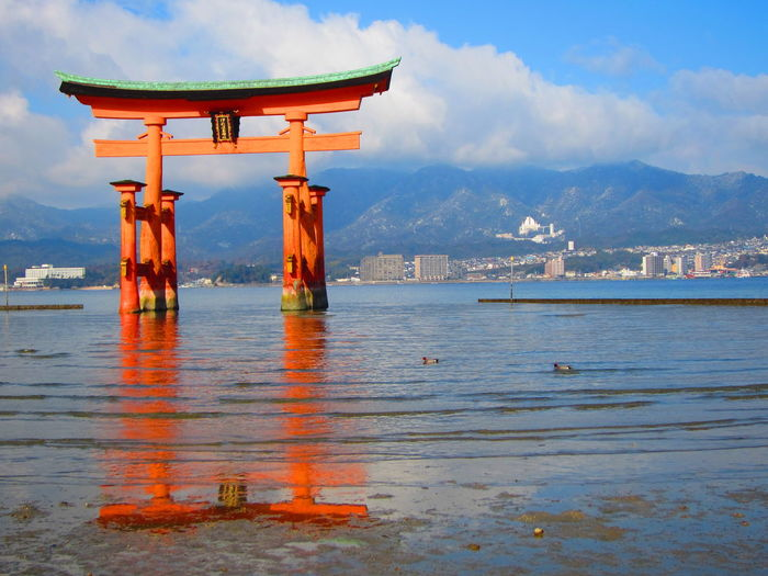 Scenic view miyajima torii gate reflected in sea against sky