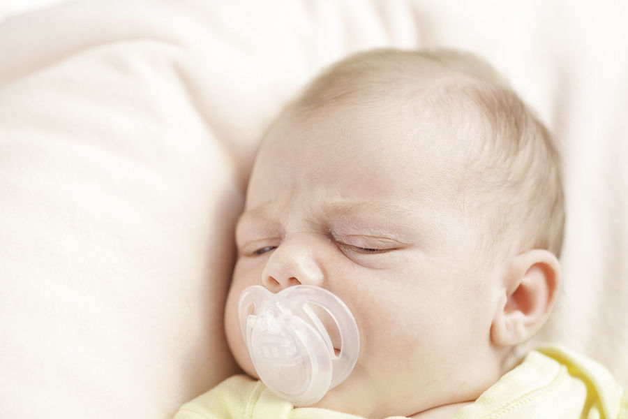 Newborn baby girl on pink background with a pacifier or dummy to comfort her for sleep in natural light. Babies Only Baby Baby Babyhood Childhood Close-up Cute Eyeem People Eyes Closed  Fragility Headshot Indoors  Innocence Lying Down Natural Light Natural Light Portrait New Life Newborn NewBorn Photography One Person Pacifier People Real People Sleeping Sucking
