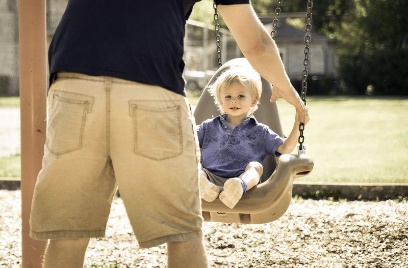 Father Pushing Child On Swing
