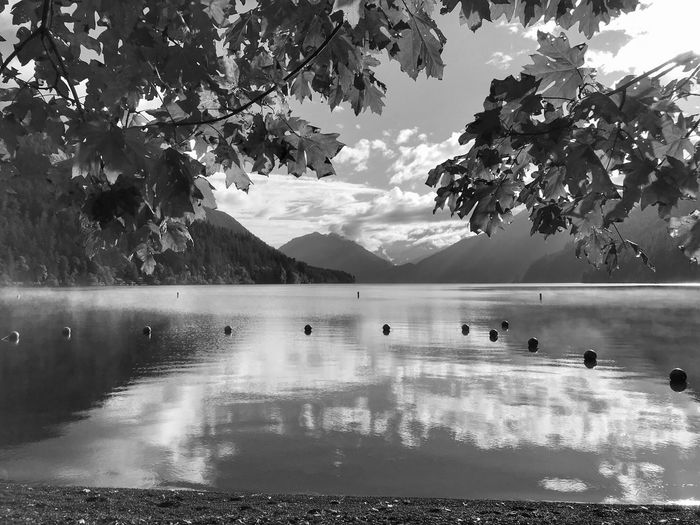 Black and white landscape of a lake, reflection of clouds and mountains in the background