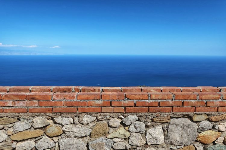 Stone wall by sea against blue sky
