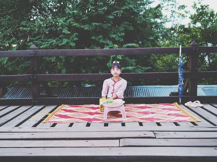 Portrait of girl sitting on railing against trees