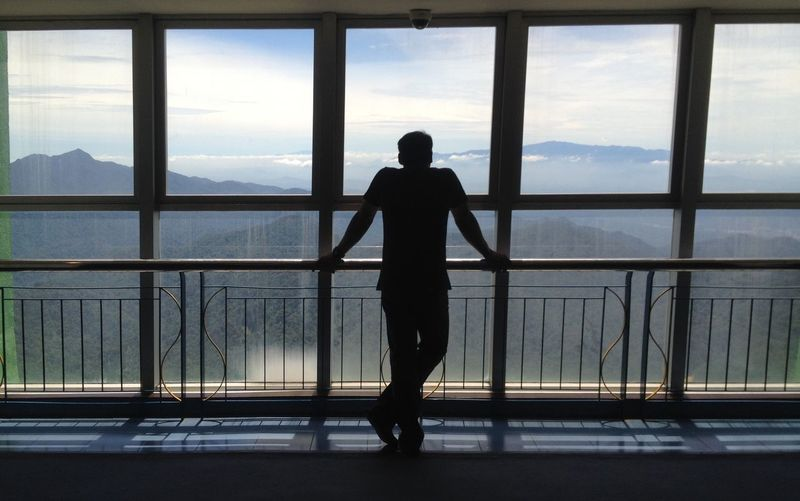 Rear view of silhouette man looking through window while standing by railing