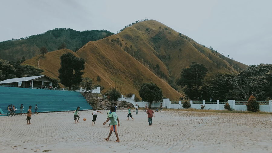 People on beach against mountains