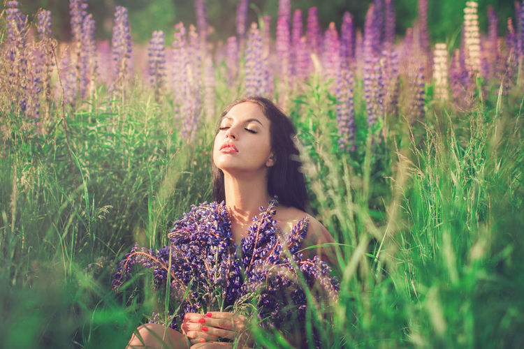 Beautiful young woman standing by purple flowers on field