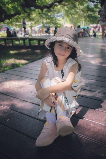 Portrait of happy girl sitting in park