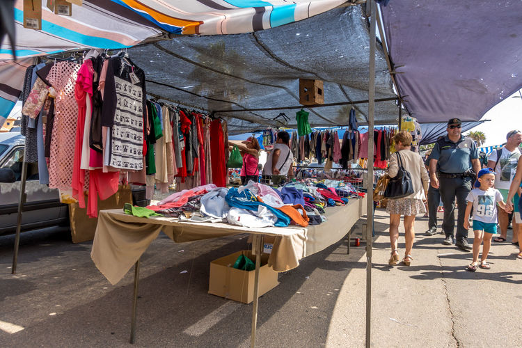 Market Choice Market Stall For Sale Hanging Variation Large Group Of Objects Textile Clothing Small Business Sale Business Retail  Real People Incidental People Street Market Sunlight Arrangement Retail Display Outdoors Consumerism Almería SPAIN Market Street Market