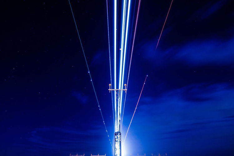 EyeEmNewHere Landing Light Lines London Plane Airport Blue Connection Electricity  Electricity Pylon Flight Illuminated Long Exposure Low Angle View Nature Neon Night No People Outdoors Sky Star - Space Symmetry Technology Vapor Trail Mix Yourself A Good Time