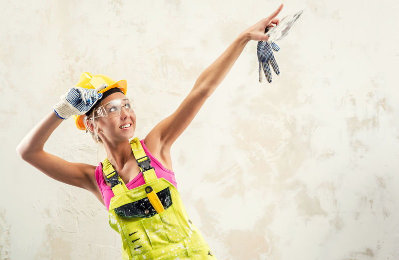 Female Worker In Coverall Pointing While Standing Against Wall
