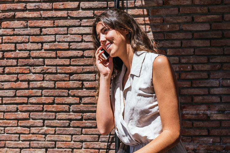 Young woman smiling while standing against brick wall