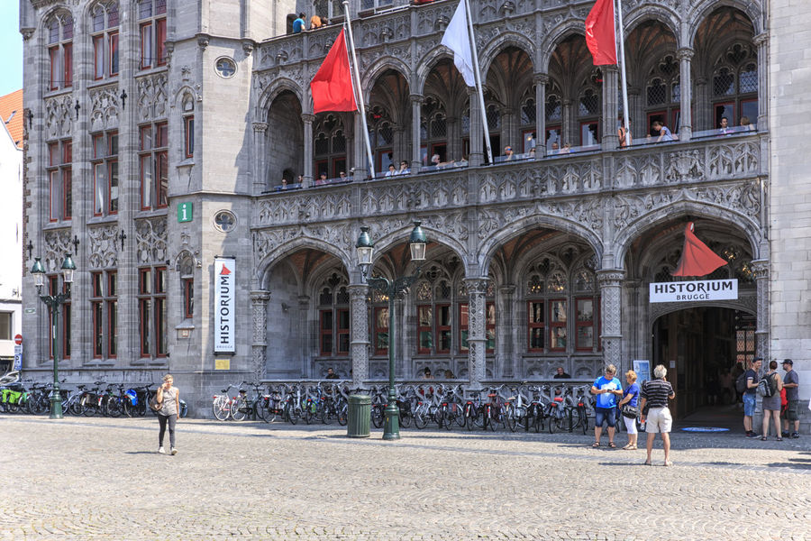 Bruges, Belgium - July 7, 2017: Tourists in front of the Historium Museum in the Market Square of Bruges Beer Belgium Brugge Chocolate Dijver Canal Duvel Flanders Panoramic View Provinciaal Hof West Flanders Aerial View Belfry Tower Bikes Bruges Europe Flower French Fries Holland Market Square Medieval Town Mussels
