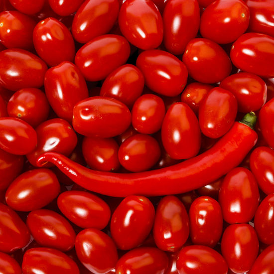 High angle view of red chili pepper on tomatoes