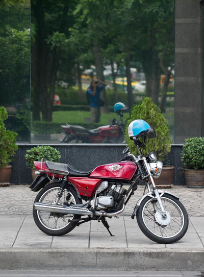 Motorcycle parked on paved walkway against glass building