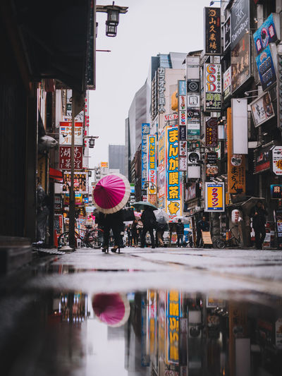 Japan Reflection Adult Architecture Building Exterior Built Structure City City Life Group Of People Lifestyles Market Men Outdoors People Rain Real People Retail  Store Street Text Umbrella Water