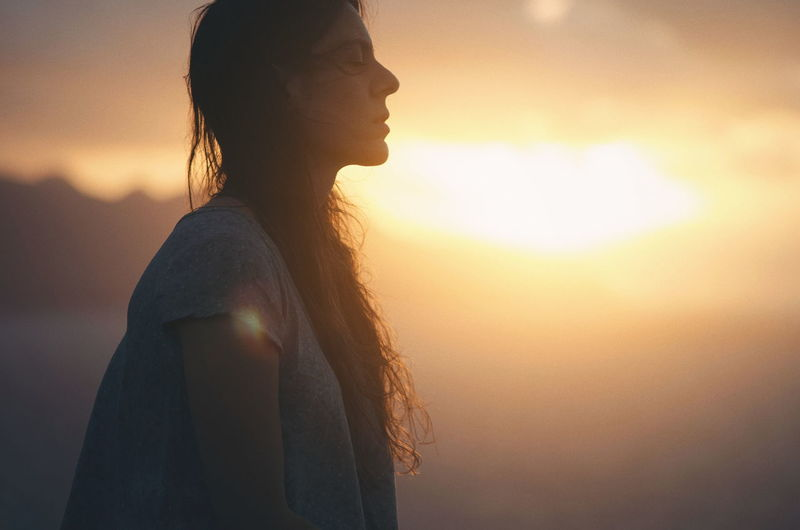 Side view of young woman standing against sky during sunset