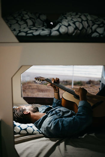 Man Holding Guitar While Lying Down On Bed At Home