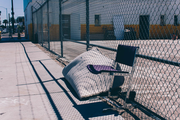 Empty chair by chainlink fence