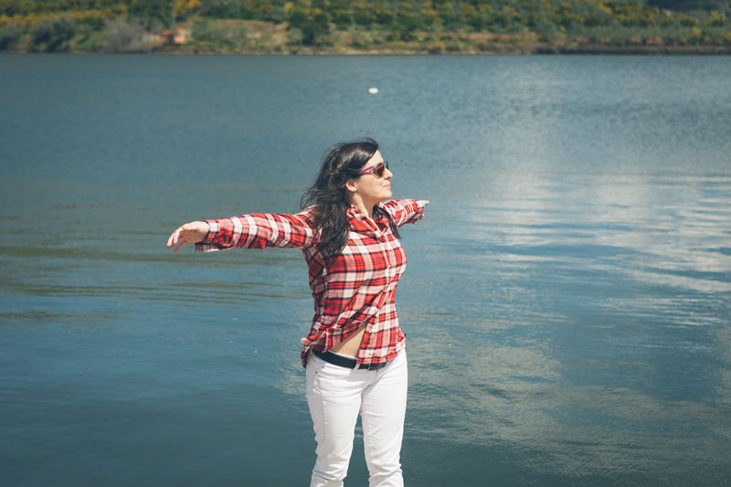 Beauty In Nature Casual Clothing Focus On Foreground In Front Of Lake Leisure Activity Lifestyles Nature Non-urban Scene Person Red Scenics Standing Summer Sunglasses Three Quarter Length Tranquil Scene Tranquility Travel Vacations Water Waterfront Weekend Activities Young Adult