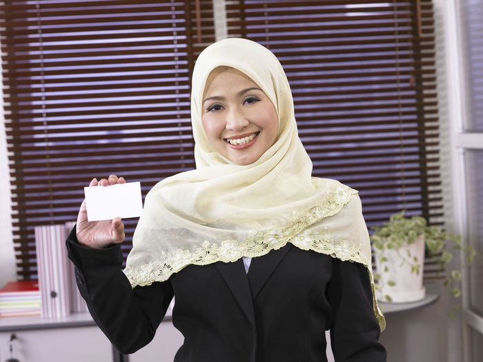 Portrait Of Businesswoman In Hijab Showing Blank Business Card In Office