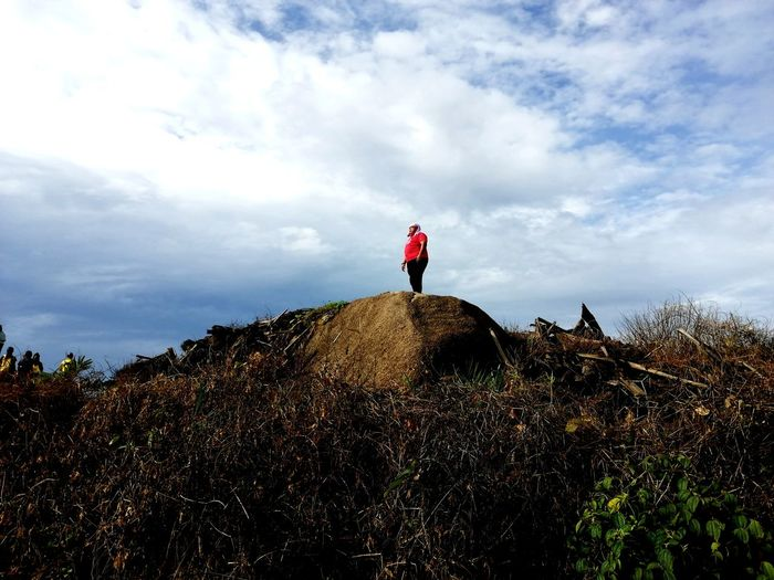 Low angle view of person standing on land against sky