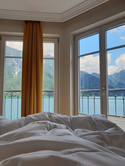 good morning Lake No People Good Morning Bedsheet Linen Beautiful Place Holidays Curtain Romantic Place Ocean View Waves Mountains The Great Outdoors - 2018 EyeEm Awards The Traveler - 2018 EyeEm Awards The Architect - 2018 EyeEm Awards Love Nest Peaceful Cozy Place At Home Bedroom Bed Home Interior Window Curtain Architecture Sky Looking Through Window Transparent Window Frame Glass