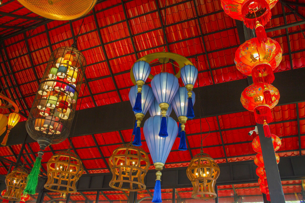 LOW ANGLE VIEW OF ILLUMINATED LANTERNS HANGING ON CEILING IN BUILDING