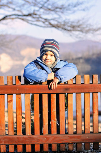 A boy standing behind the railing. Autumn Colors Behind The Railing Boy Portrait Childhood Memories Cold Temperature Elementary Age Flashback Headware Kid Photography Kidsphotography Knit Hat Mountain And Lake Protection Railing Railing Safety Unreachable Warm Clothing Wooden Railing