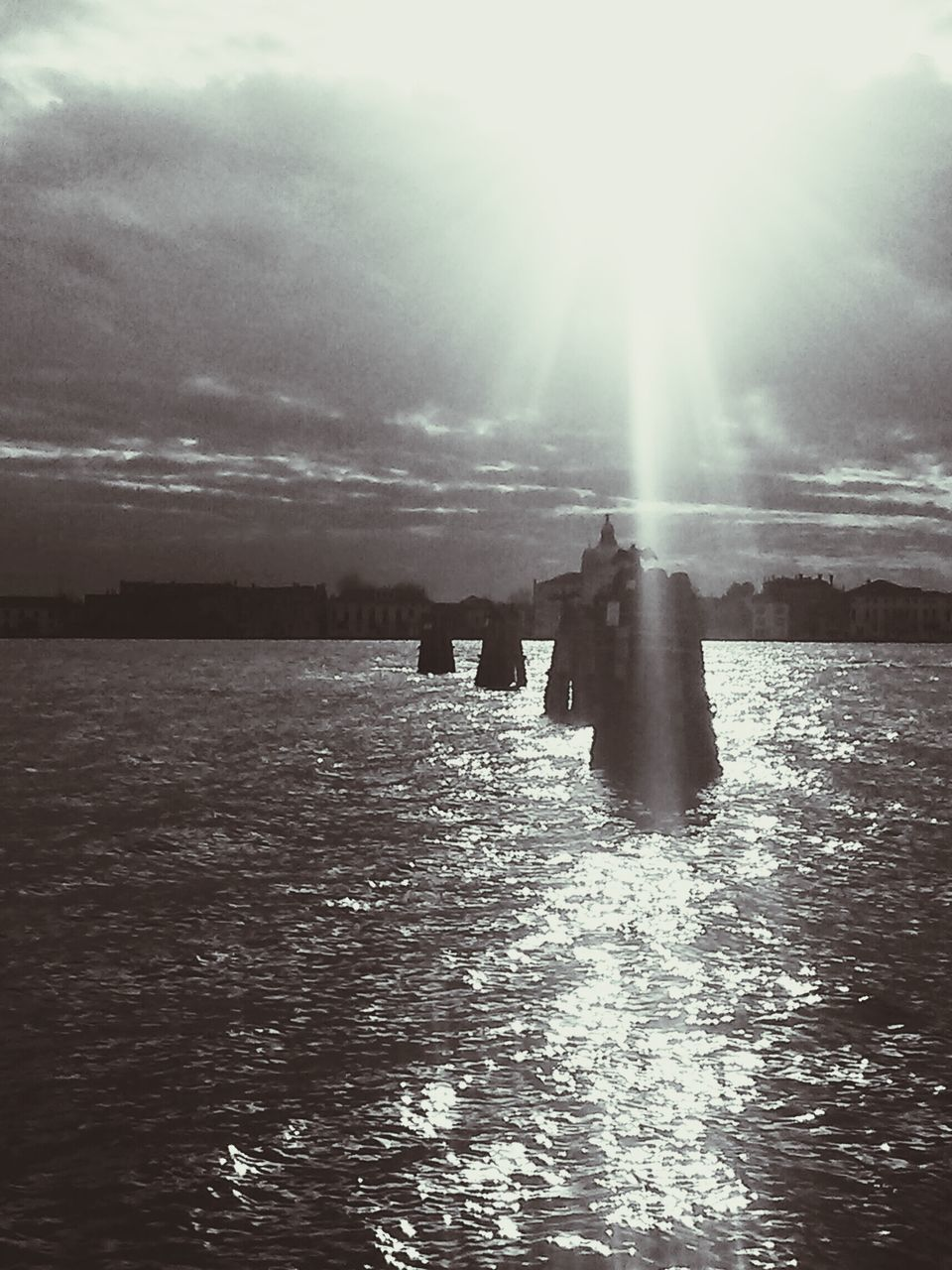 water, sunbeam, nature, waterfront, lens flare, tranquility, sunlight, beauty in nature, scenics, tranquil scene, outdoors, sea, sky, day, silhouette, sun, real people