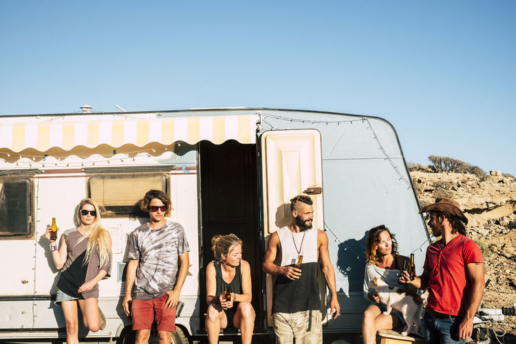 Group of young people alternative millennial young men and women standing outside a vintage caravan enjoying the sunny day of summer outdoor leisure activity together in friendship Sky Clear Sky Group Of People Real People Women Sunlight Day Lifestyles Men Casual Clothing Nature People Copy Space Architecture Leisure Activity Adult Togetherness Friendship Standing Outdoors Teenager Adolescence  Caucasian Enjoying Life Freedom Drink Drinking Beer Mountain Range Caravan Camping Relaxation Vintage Old Backgrounds Blue Sky Sunlight Bright Vacations Beauty In Nature Beautiful People