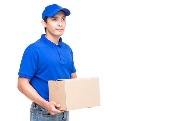 Salesman with cardboard box standing against white background