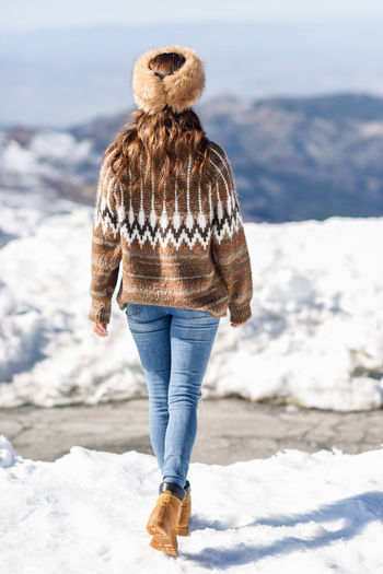 Rear view of woman walking on snow covered land during winter