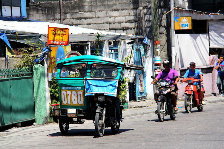 People driving vehicles on city street
