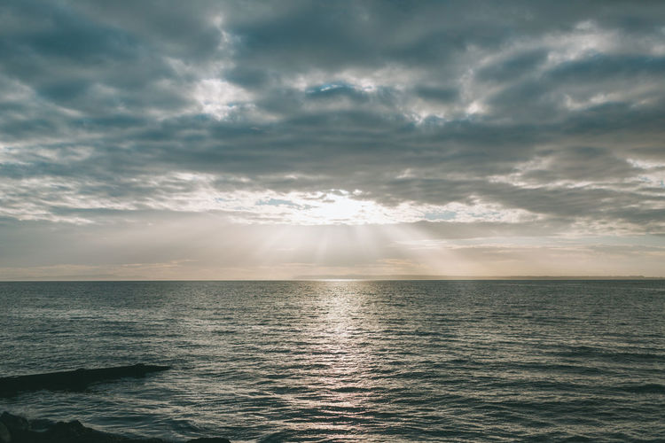 Sun rays coming through the clouds over the ocean. Sunlight No People Nature Sunset Tranquil Scene Waterfront Horizon Horizon Over Water Tranquility Scenics - Nature Beauty In Nature Water Sea Cloud - Sky Sky
