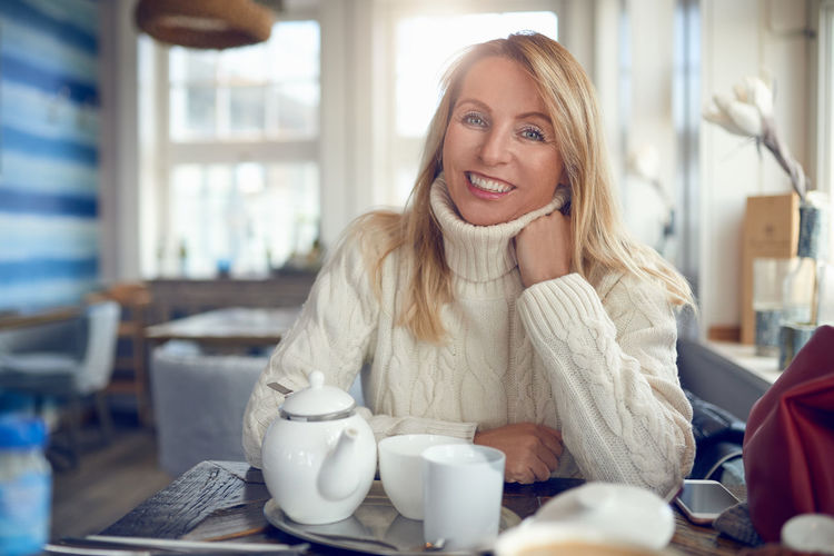 Portrait Of Smiling Woman Sitting With Coffee On Table At Home