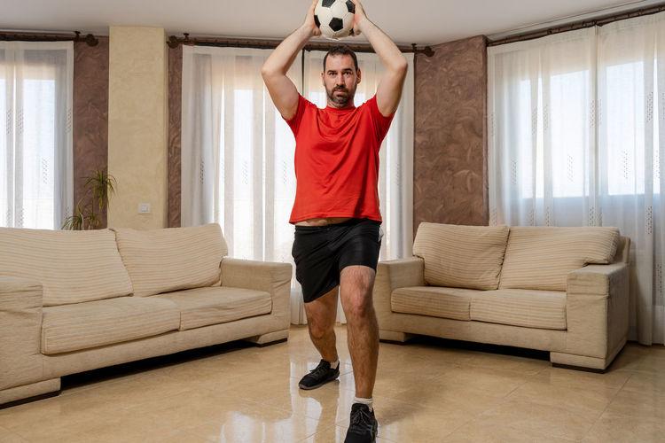 Full length of man standing on sofa