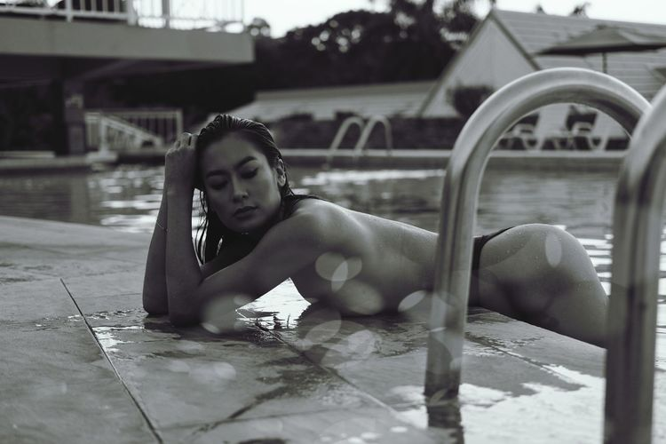 Portrait of young woman lying on swimming pool
