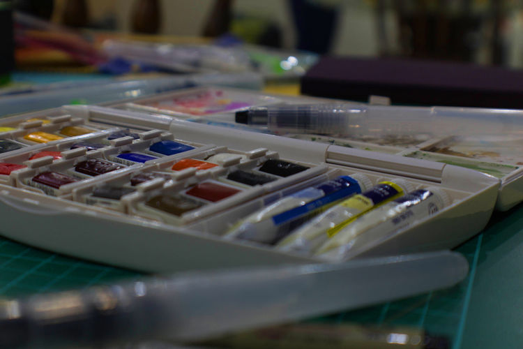Close-up of paint tube by paintbrushes on table