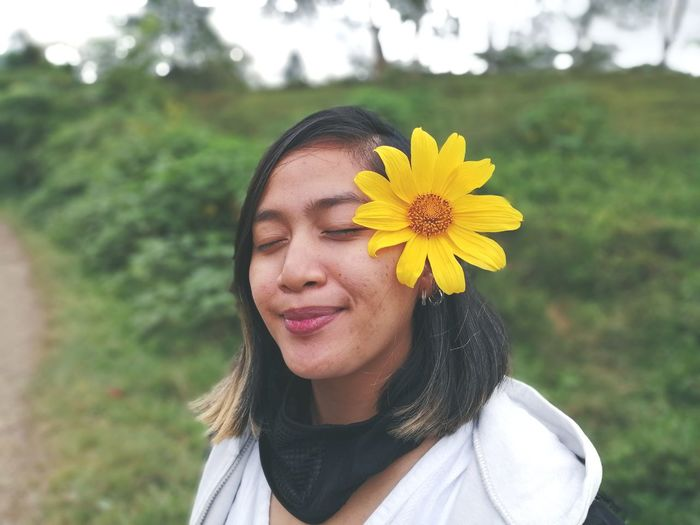 Woman with yellow flower and eyes closed on field