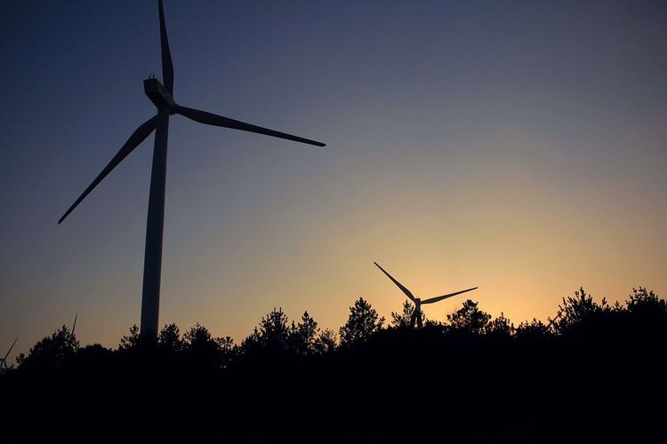 Low angle view of wind turbine against sky at dusk