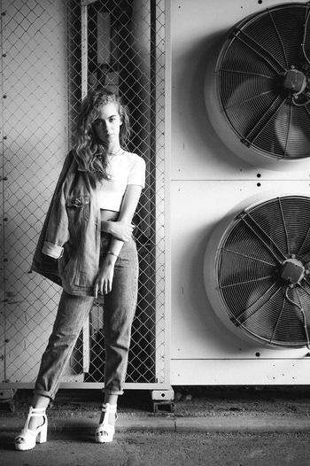 Portrait of teenage girl standing against exhaust fans