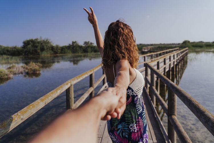 Woman holding hand of boyfriend while standing on footbridge against sky