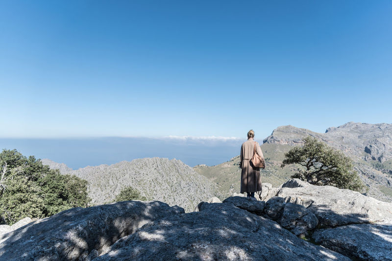 Adult Adults Only Adventure Alone Beauty In Nature Blue Clear Sky Day Full Length Mallorca Mountain Top Nature One Person One Woman Only Only Women Outdoors Overcoat People Serra De Tramuntana Sky Standing Tranquility Travel Wanderlust