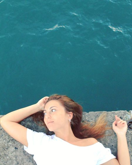 High angle view of young woman relaxing at seaside