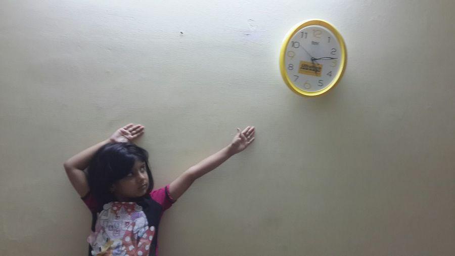 Girl reaching towards clock mounted on wall