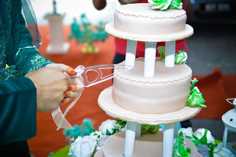 Midsection of couple cutting wedding cake