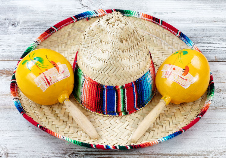 Close up view of traditional maracas and a large sombrero for Cinco de Mayo holiday celebration on weathered white wooden boards Celebration Cinco De Mayo Holiday Mexico Music Fiesta Maracas Mexican Party Sombrero