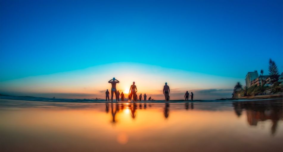 Silhouette people by sea against clear blue sky during sunset