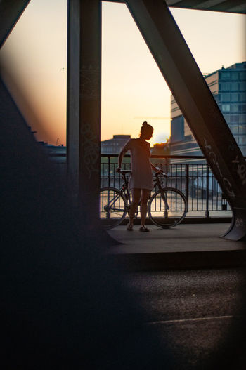 Woman standing by bicycle on bridge in city during sunset