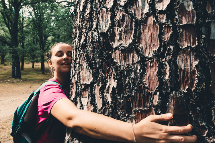 Portrait of woman holding smart phone by tree